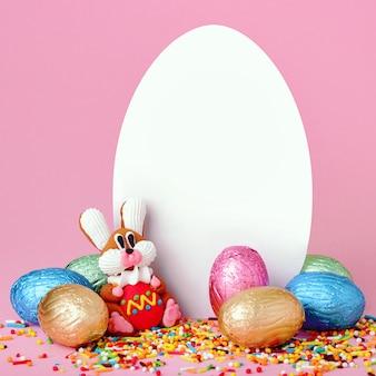 Kompozycja wielkanocna. słodkie kwiaty, słodki króliczek i czekoladowe jajka w folii na różowym tle z białym pustym arkuszem papieru w kształcie jajka.