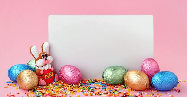 Kompozycja wielkanocna. słodkie kwiaty, słodki króliczek i czekoladowe jajka w folii na różowym tle z białym pustym arkuszem papieru w kształcie ramki.