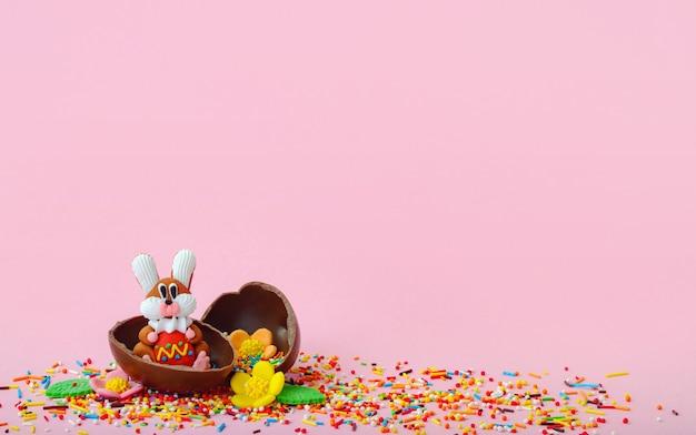 Kompozycja wielkanocna. słodkie kwiaty, słodki króliczek i czekoladowe jajka w folii na różowym tle z pustym miejscem na inspirację.