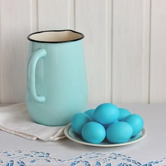 Kompozycja wielkanocna z emaliowanym na niebiesko dzbanem i malowanymi jajkami na talerzu