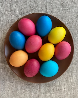 Kompozycja wielkanocna z kolorowymi jajkami na brązowym talerzu na stole