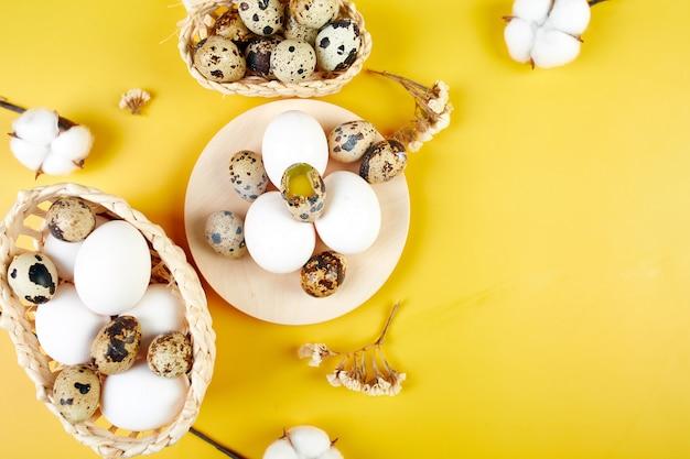 Kompozycja wielkanocna z kwiatami bawełny i pisankami w koszyczku na żółtym tle. wesołych świąt wielkanocnych, kopia przestrzeń.