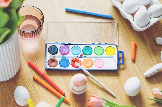 Kompozycja wielkanocna z narzędziami do malowania jajek i kwiatów na drewnianym stole. widok z góry.