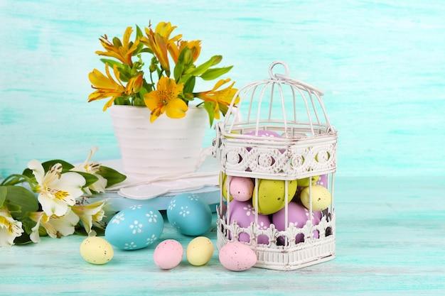 Kompozycja wielkanocna z pisankami w ozdobnej klatce i kwiatach, na kolorowym drewnianym stole