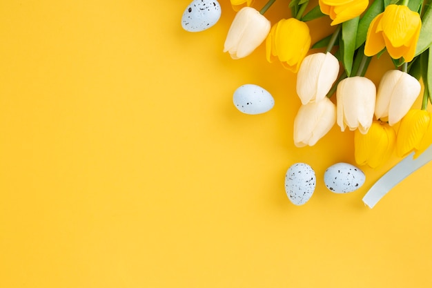 Kompozycja wielkanocna z tulipanów i pisanek na żółtym tle z miejsca na kopię