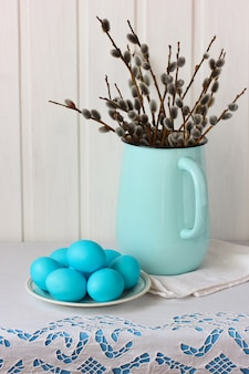 Kompozycja wielkanocna z wierzbami w emaliowanym dzbanku i niebieskimi jajkami na talerzu