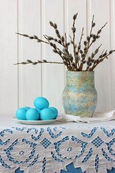 Kompozycja wielkanocna z wierzbami w wazonie i niebieskimi jajkami na talerzu na stole z koronkowym obrusem