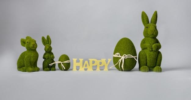Kompozycja wielkanocna z zającem i jajkami w kolorze zielonym na szarym tle, miejsce na tekst