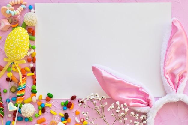 Kompozycja wielkanocna ze słodyczami, uszami królika i tulipanami. kartkę z życzeniami wesołych świąt.