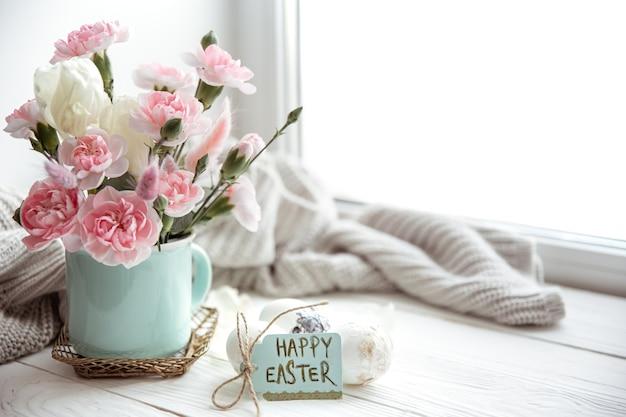 Kompozycja wielkanocna ze świeżych kwiatów w wazonie i napisem wesołych świąt na przestrzeni kopii karty.