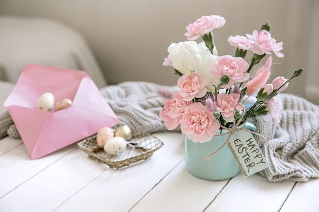 Kompozycja wielkanocna ze świeżymi kwiatami w wazonie, dzianiną i napisem wesołych świąt na kartce.