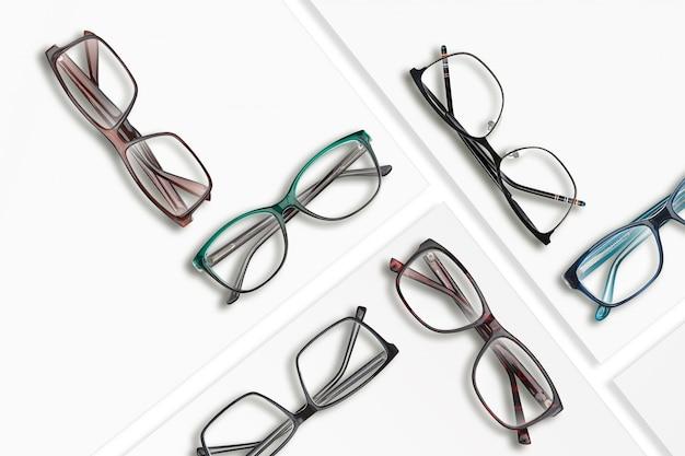 Kompozycja wielu różnych klasycznych okularów na białych kwadratowych stojakach. zdjęcie studyjne.