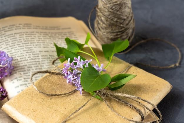 Kompozycja wiosenna. ładne pudełko prezentowe owinięte brązowym papierem rzemieślniczym i ozdobione bukietem bzu leży na otwartej książce na ciemnym tle.