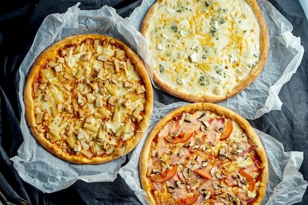 Kompozycja z 3 różnymi pizzami: 4 serami, hawajską i szynką na pergaminie na ciemnym stole. włoska pizza z pieca
