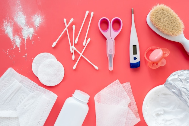 Kompozycja z akcesoriami dla dzieci i kosmetykami do pielęgnacji dziecka na różowym tle, płaskie mieszkanie, widok z góry, układ. modne tło, higiena noworodków.