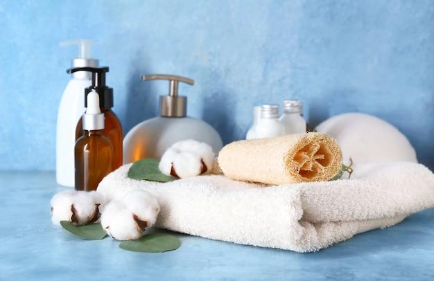 Kompozycja z akcesoriami do kąpieli, kosmetykami i bawełnianymi kwiatami na kolorowej powierzchni