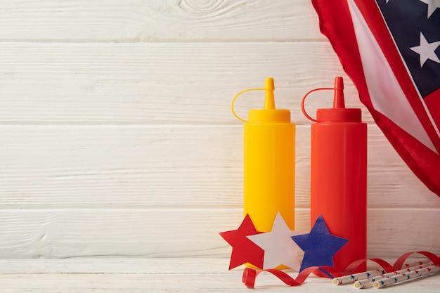 Kompozycja z amerykańską flagą, butelki na sos i kolorowe gwiazdki na drewnianym
