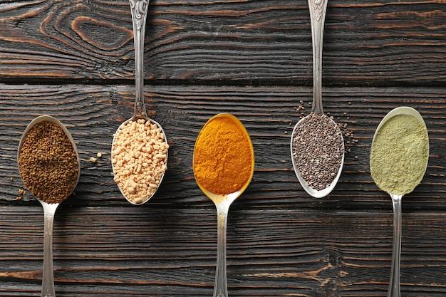 Kompozycja z asortymentem produktów superfood w łyżkach na drewnianej powierzchni, widok z góry