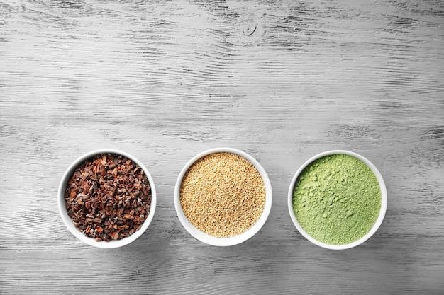Kompozycja z asortymentem produktów superfood w miskach na jasnym drewnianym tle, widok z góry