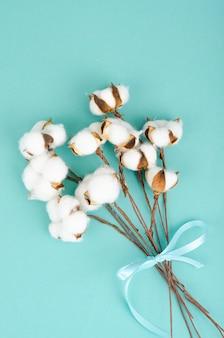 Kompozycja z bawełnianymi kwiatami na jasnej powierzchni