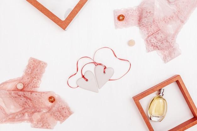 Kompozycja z białymi sercami wraz z różową wstążką, damska bielizna koronkowa, perfumy na białym koncepcja wakacyjna na ślub, walentynki, romantyczna relacja.