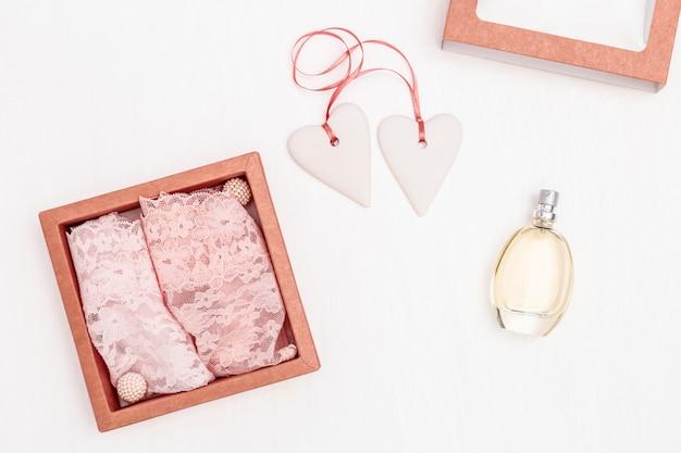 Kompozycja z białymi sercami wraz z różową wstążką, damską koronkową bielizną i perfumami
