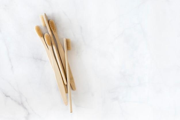Kompozycja z biodegradowalnymi szczoteczkami bambusowymi na marmurze, widok z góry