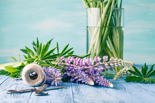 Kompozycja z bukietem kwiatów niebieskich łubinów, starych rustykalnych nożyczek