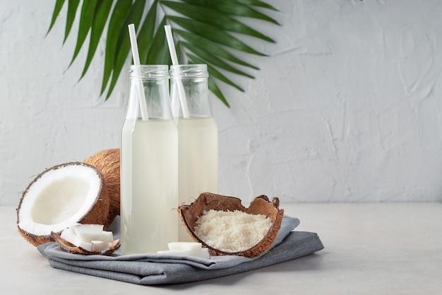 Kompozycja z butelkami orzeźwiającej wody kokosowej na lekkim stole, miejsce na tekst