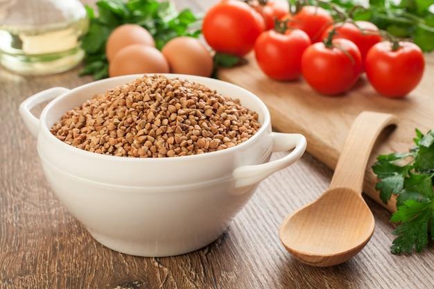 Kompozycja z ceramiczną miską suchej gryki, jajek, pomidorów i pietruszki w tle.