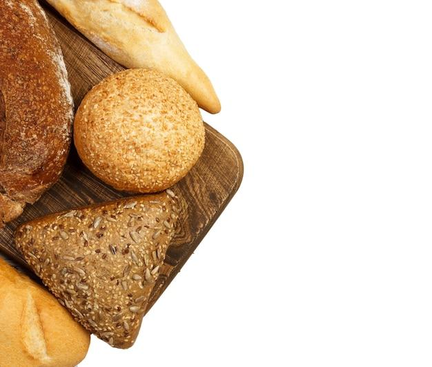 Kompozycja z chleba i bułek na deska do krojenia na białym tle.