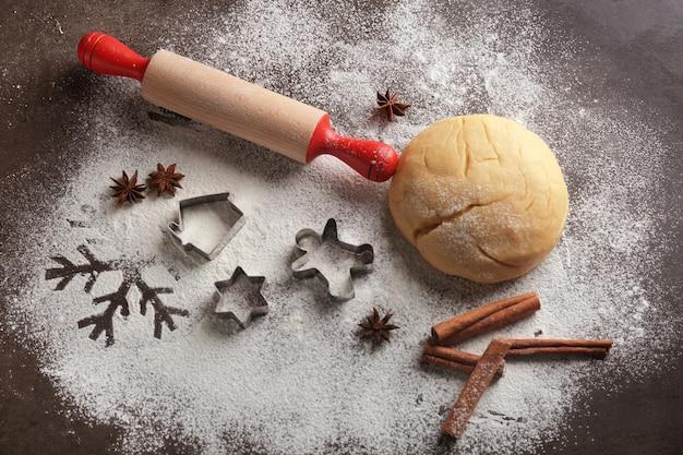 Kompozycja z ciastem i foremkami na świąteczne ciasteczka na stole