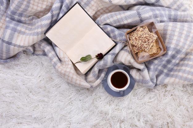 Kompozycja z ciepłą kratą, książką, kubkiem gorącego napoju na kolorowym tle dywanu