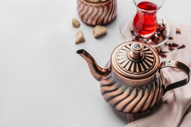 Kompozycja z czajnikiem i szklanką herbaty na jasnym tle