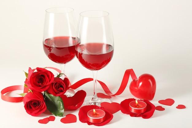Kompozycja z czerwonym winem w kieliszkach, czerwonych różach, wstążce i ozdobnych serduszkach