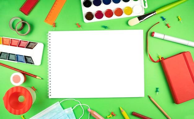 Kompozycja z czystą kartką papieru i farbami