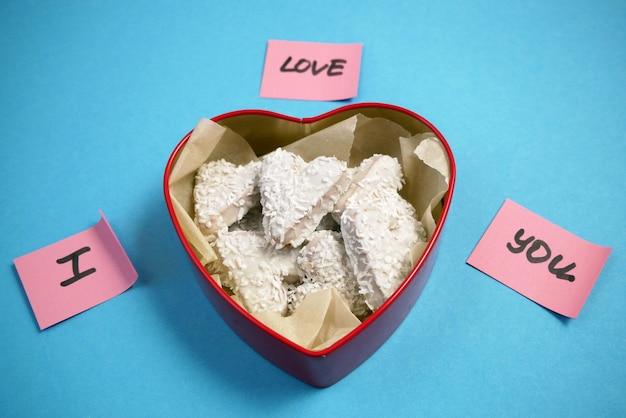 Kompozycja z dekorowanymi ciasteczkami w kształcie serca w pudełku z uroczymi papierowymi naklejkami
