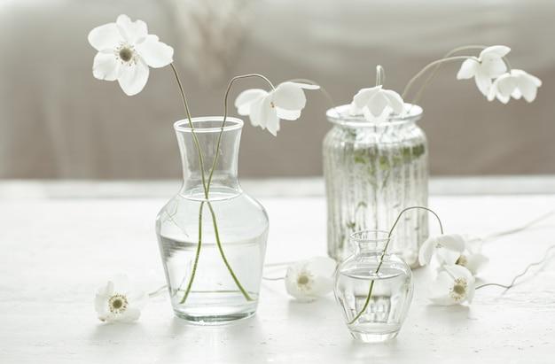 Kompozycja z delikatnymi wiosennymi kwiatami w szklanych wazonach na rozmytym tle
