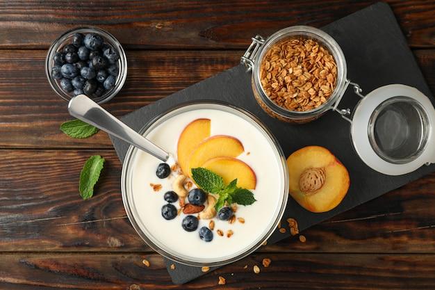 Kompozycja z deserem jogurtowym i składnikami na drewnianym tle,