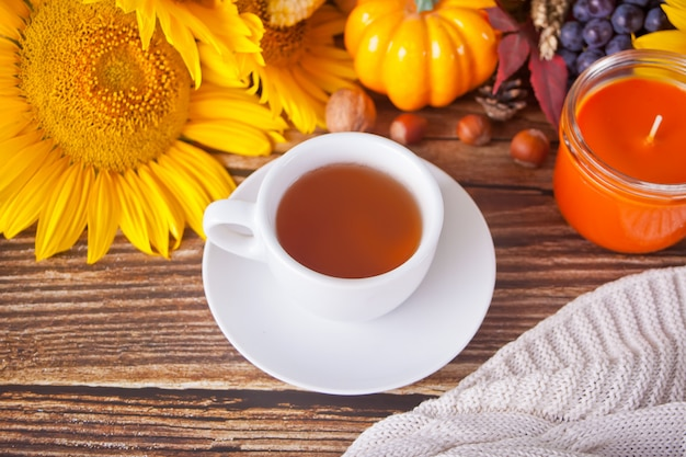 Kompozycja z dyni, jesiennych liści, słonecznika, filiżanki herbaty, kratki i jagód na drewnianym stole