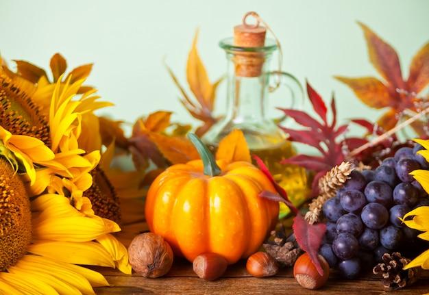 Kompozycja z dyni, jesiennych liści, słonecznika i jagód na drewnianym stole