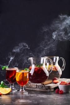 Kompozycja z dzbanami i szklankami z gorącymi napojami, owocami, jagodami i miętą.