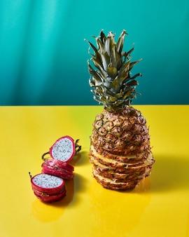 Kompozycja z egzotycznymi tropikalnymi owocami pojedynczego ananasa i smoczego owocu, pitaya złożona z plasterków na bichromicznym żółto-zielonym tle.