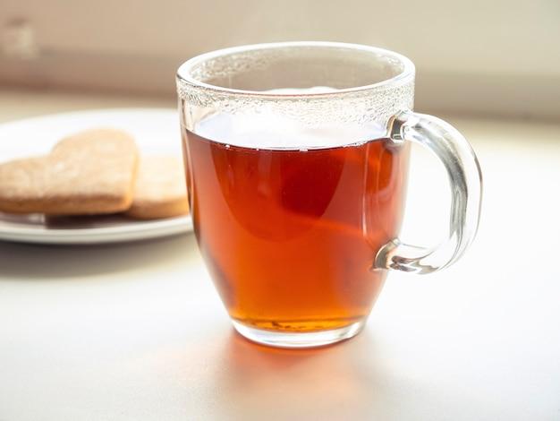 Kompozycja z filiżanką czarnej herbaty i herbatnikiem talerzowym na parapecie