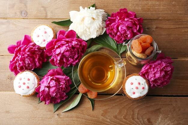 Kompozycja z filiżanką herbaty ziołowej i kwiatami piwonii na drewnianej powierzchni
