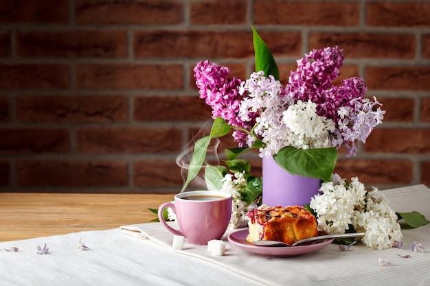 Kompozycja z gałęzi bzu i filiżankę kawy na drewnianym stole