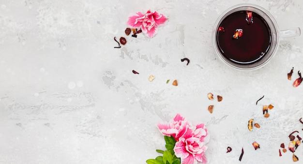 Kompozycja z gorącą herbatą z hibiskusa w szklanym kubku z różowymi kwiatami i suszonymi listkami herbaty. widok z góry.