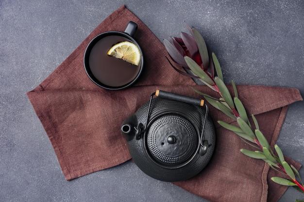 Kompozycja z imbrykiem i filiżanką herbaty w ciemnej przestrzeni