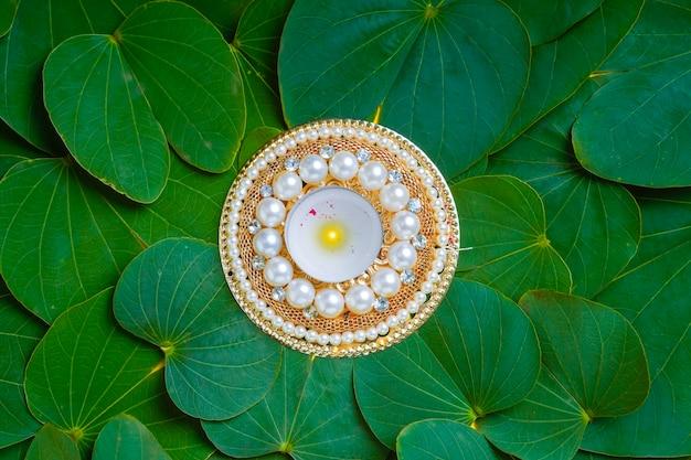 Kompozycja z indyjskiego festiwalu dusera z zielonym liściem, kwiatami i lampą