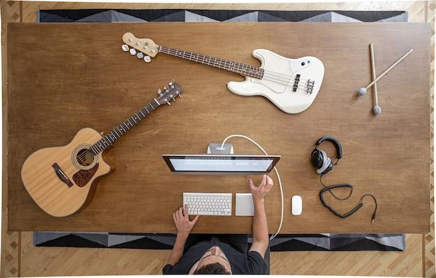 Kompozycja z instrumentami muzycznymi na dużym drewnianym stole w studiu nagrań. miejsce pracy muzyka do pracy nad dźwiękiem.